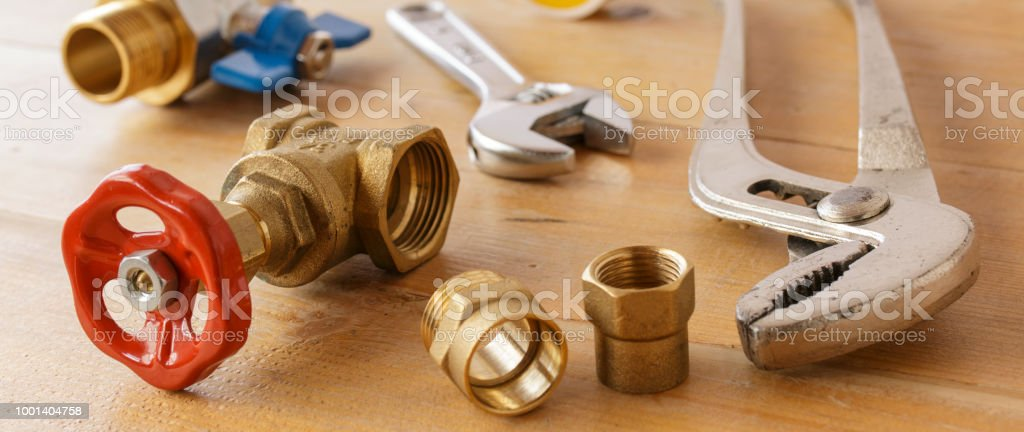 Adjustable Spanner, Vice Grip, and Water Valves on Wooden Surface Banner Image stock photo