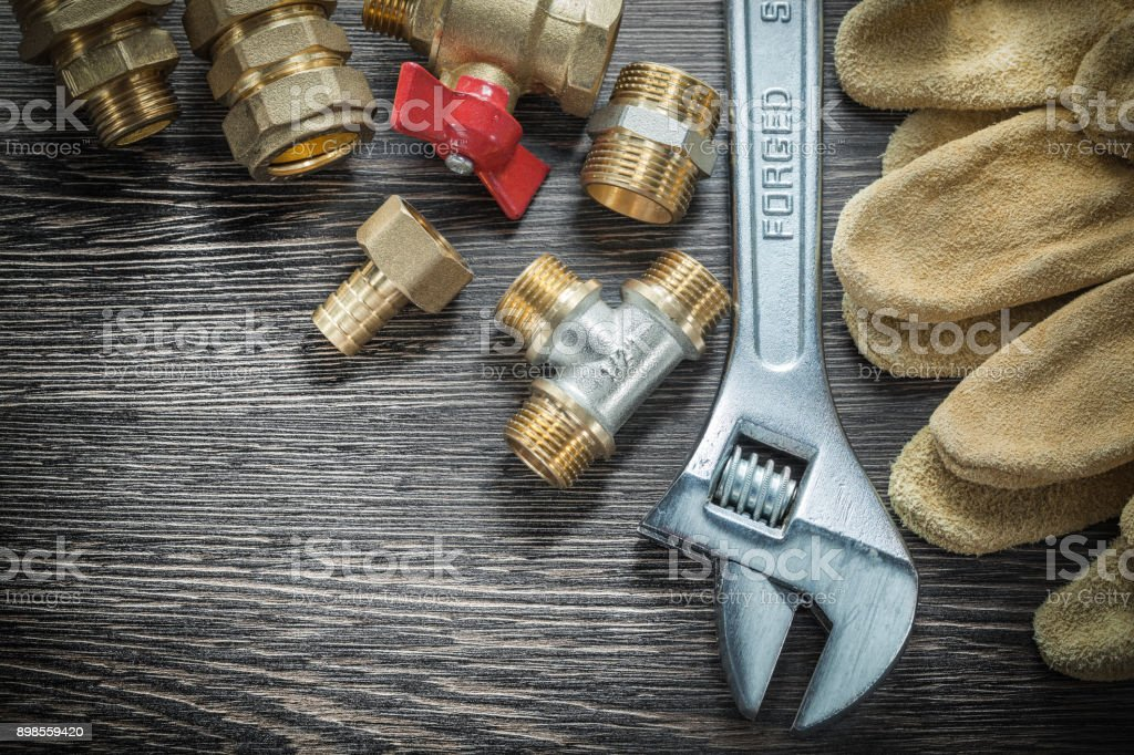Adjustable wrench water valve pipe fittings safety gloves on wooden...