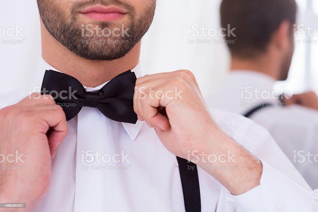 Adjusting his bow tie. stock photo