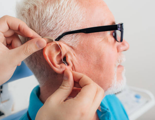 adjusting of a hearing aid for an aged man - sordità foto e immagini stock