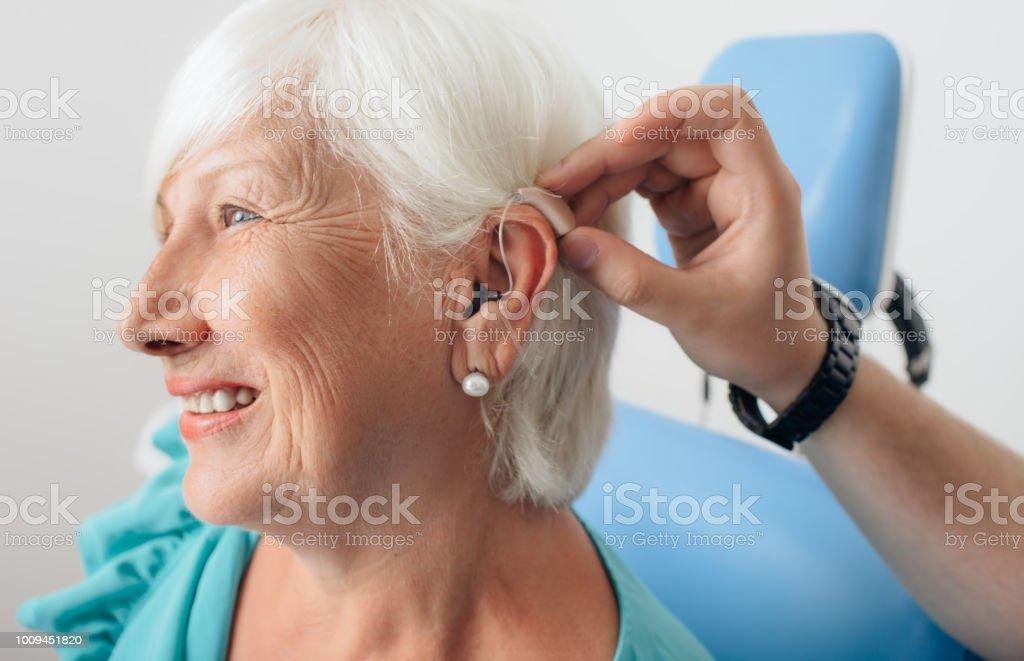 老年婦女助聽器的調整 - 免版稅65歲到69歲圖庫照片