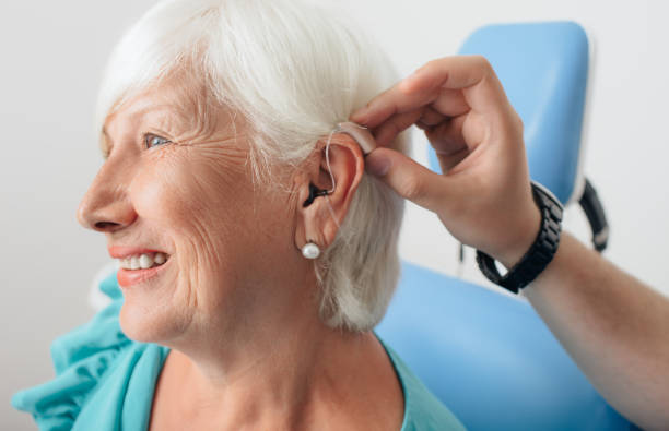 adjusting of a hearing aid for an aged woman - hearing loss stock pictures, royalty-free photos & images