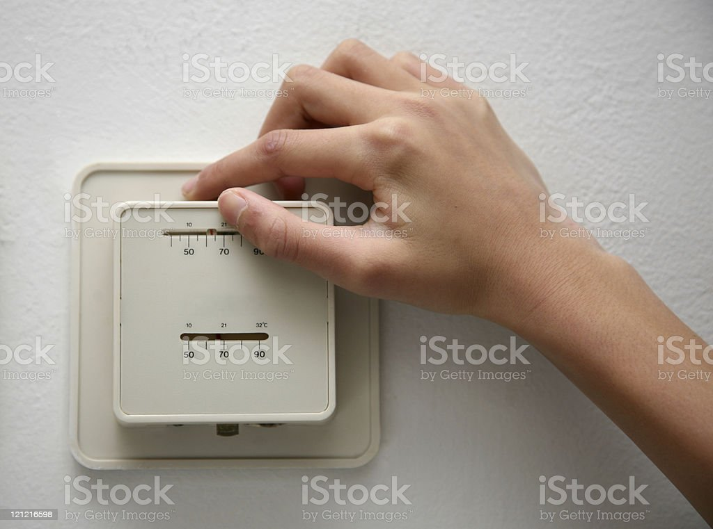 Adjusting Temperature on an Old Thermostat royalty-free stock photo