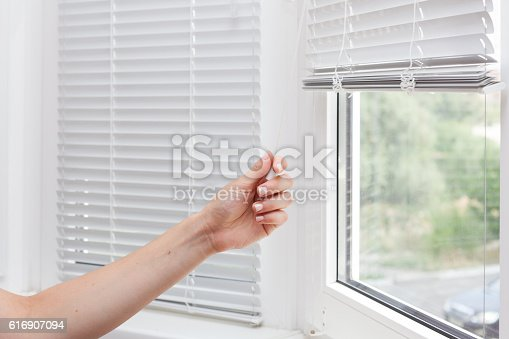 Adjusting the white blinds in height use a cord