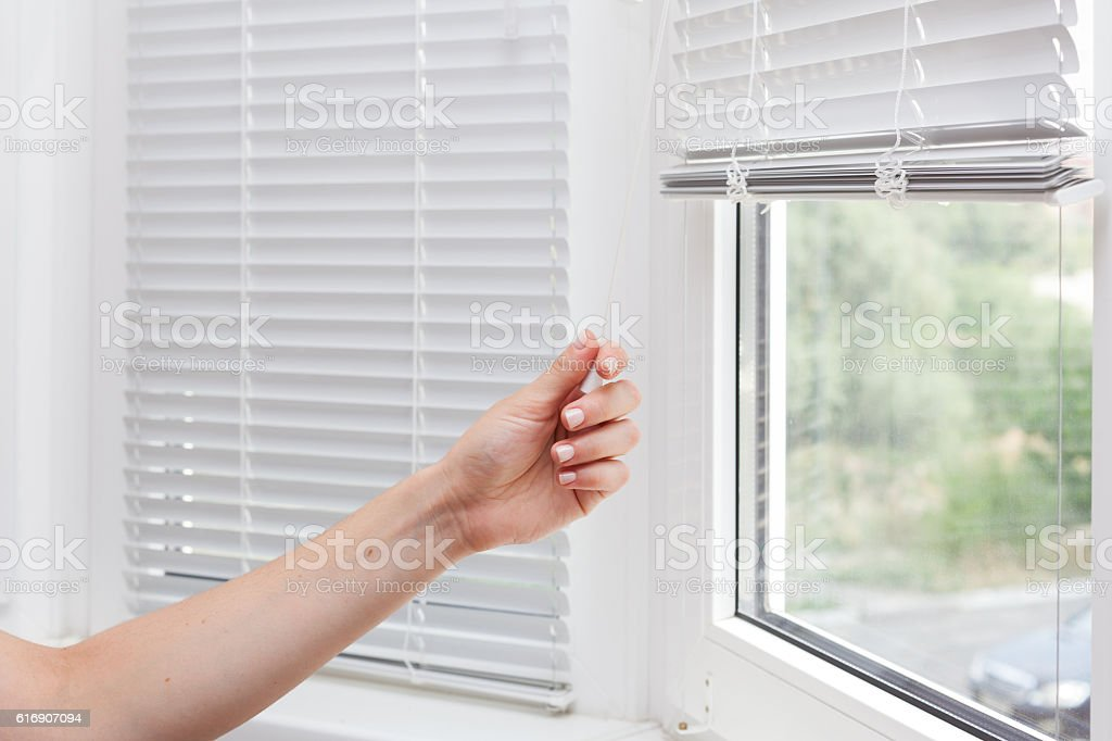 Adjusting the white blinds in height use a cord stock photo