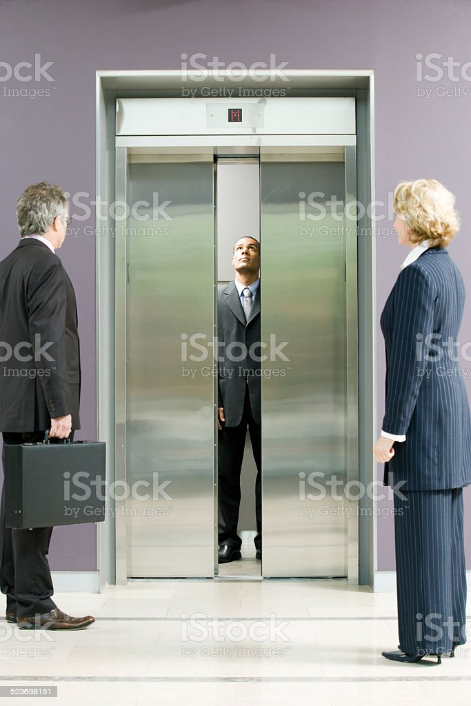 Administrative workers waiting for elevator stock photo