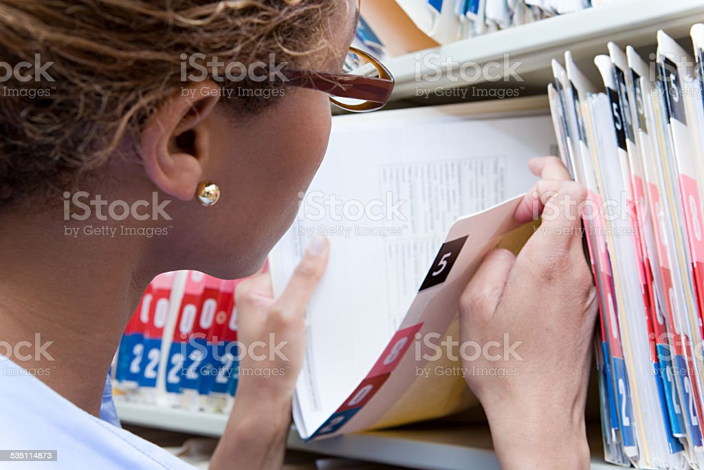 Administrator looking at medical record stock photo