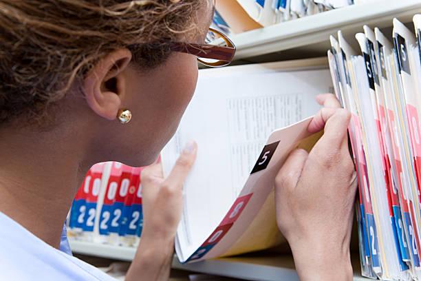 administrador olhando no registro médico - pilha arranjo - fotografias e filmes do acervo