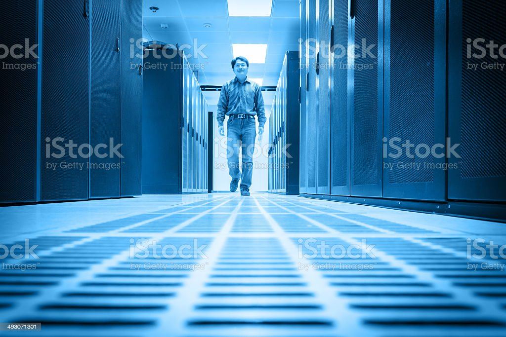 Administrator walking in the data center room royalty-free stock photo