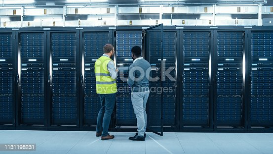 1131208605 istock photo IT Administrator with a Laptop Computer in High Visibility Vest and Black Male Engineer are Talking in Data Center while Standing Before a Server Rack. Running Diagnostics or Doing Maintenance Work. 1131198231