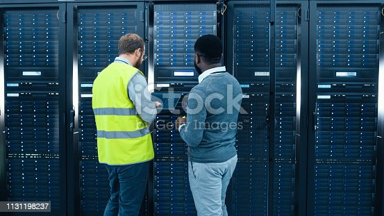 1131198396 istock photo IT Administrator with a Laptop Computer in High Visibility Vest and Black Male Engineer are Talking in Data Center while Standing Before a Server Rack. Running Diagnostics or Doing Maintenance Work. 1131198237