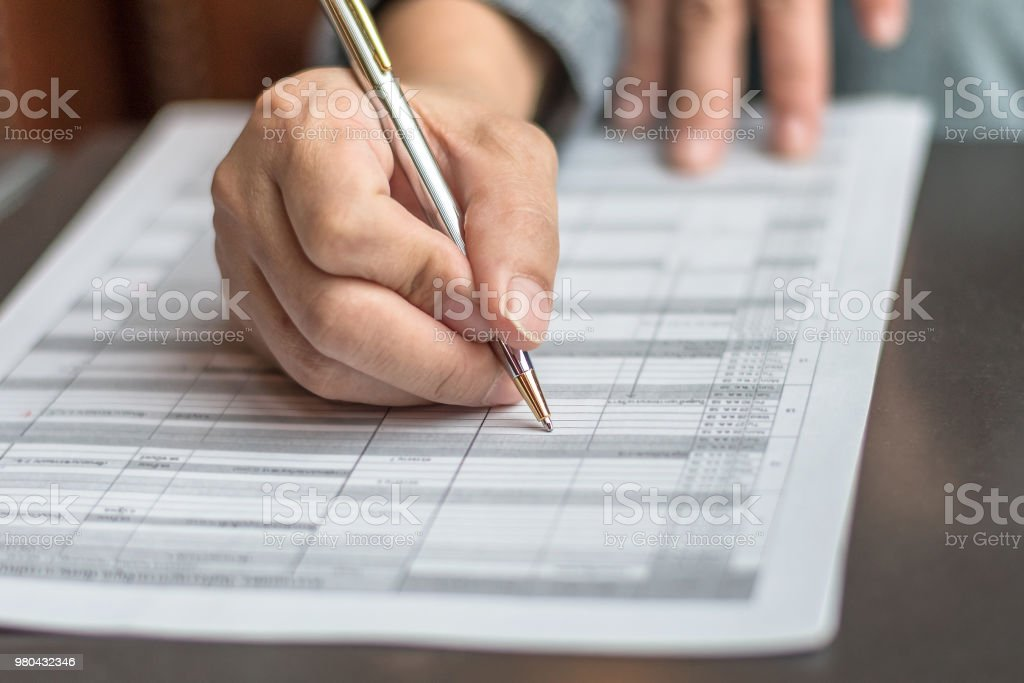 Administrator's hand fill in business schedule form document writing on yearly work plan, monthly timetable sheet, or weekly time table paper for office tasks, things and jobs to do list - Foto stock royalty-free di Accordo d'intesa