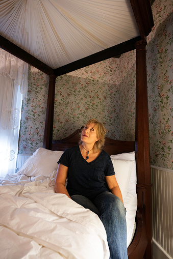 Woman in sits on a romantic rare 1880 Mallard antique four-poster bed and looks up at the fabric canopy, T'Frere's B&B, a Cajun 1880 Acadian colonial home made of red cypress, Lafayette, Louisiana, USA