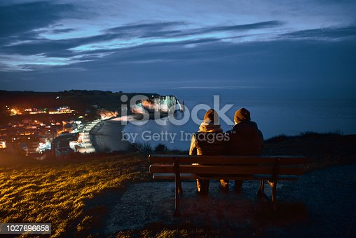 rear view of couple sitting on bench in Etretat region in night time, admiring the city.