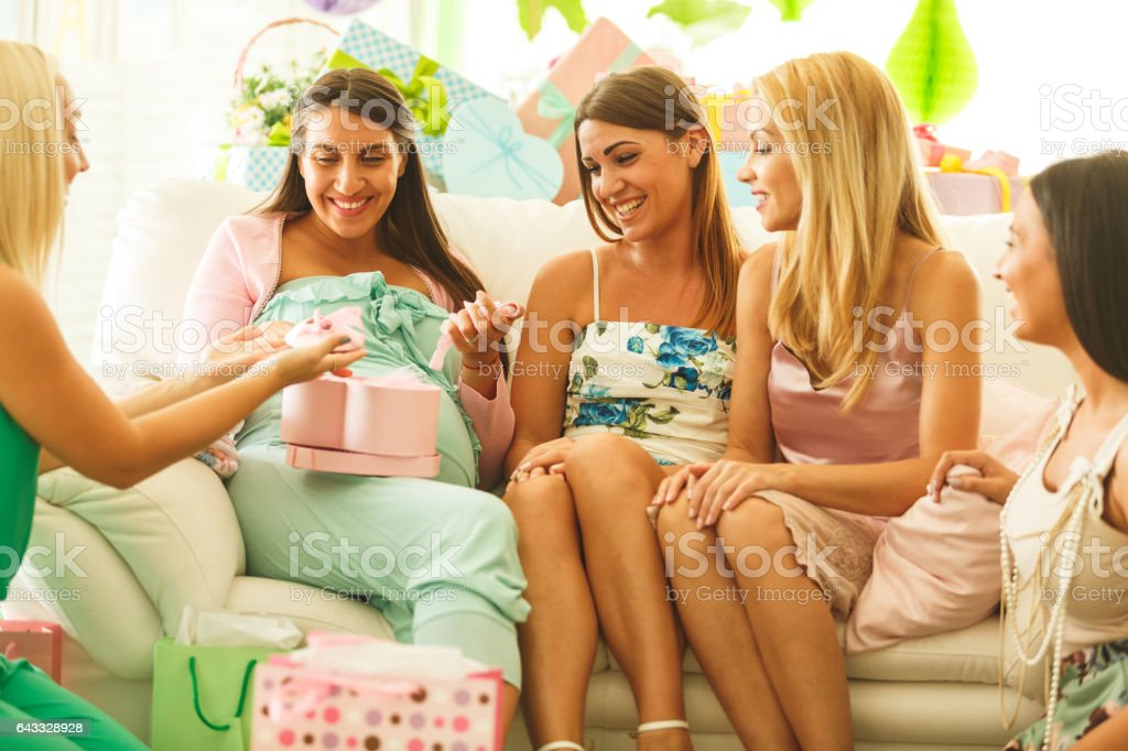 Admiring baby clothing at baby shower stock photo