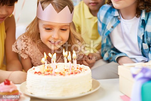 Lovely little girl and her friends looking at burning birthday candles