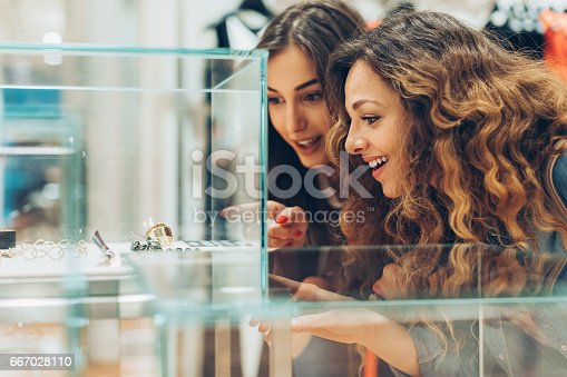 Close-up of two young women looking at expensive jewelry in the fashion store