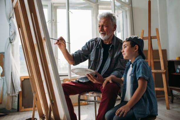 Admiring his grandpa's painting skills stock photo