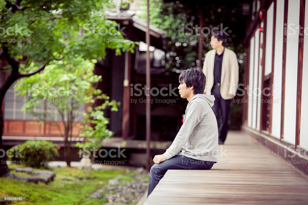 Two Japanese tourists admire the tranquil rock garden at a Temple