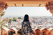 A young woman looks out over the city of Udaipur, Rajasthan, North India.