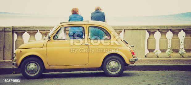 Caucasian senior couple standing by the old railing and admiring Naples bay. Old Fiat 500 parked in front of them.