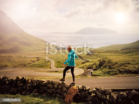 Shot of a carefree young woman walking on a short stonewall with a breathtaking view in the background