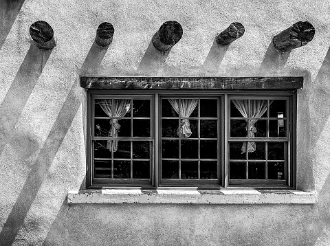 Windows and support beams on a Adobe building in Taos, New Mexico