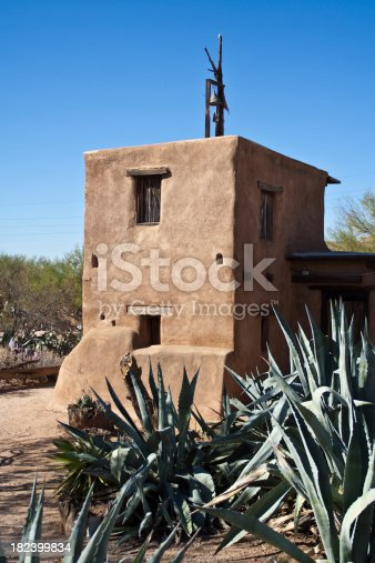 Old adobe chapel in Arizona with agave plants in the foreground.
