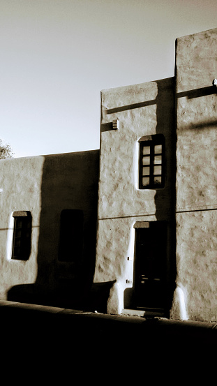 Black and white of adobe house in New Mexico during sunset.