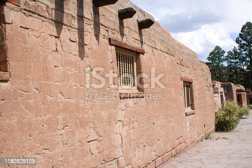 closeup of an adobe exterior house or group of houses with the vanishing point looking from behind containing windows and wooden posts sticking out the tops of the walls