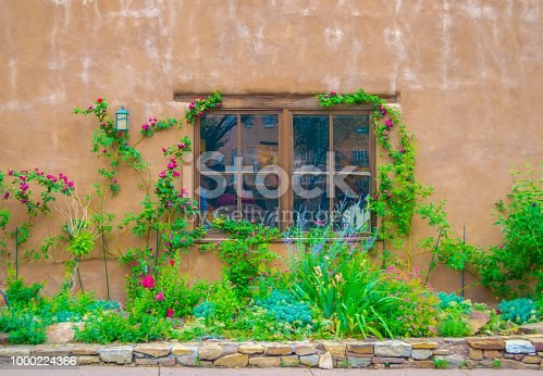 Attractive adobe wall and window with decorative garden in New Meixco