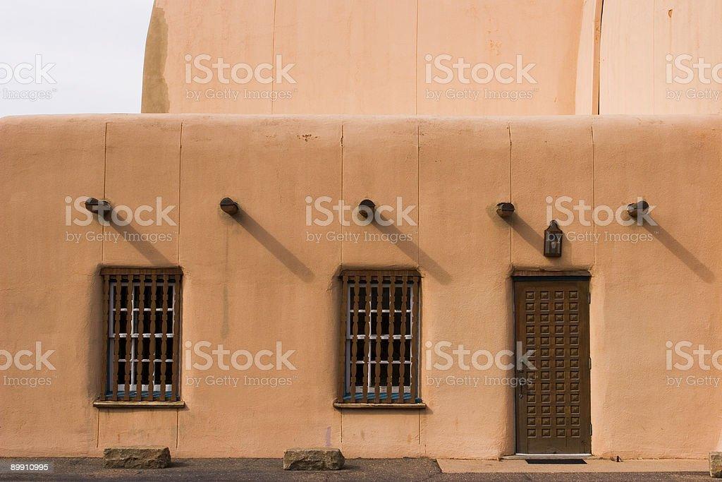 Adobe wall, window, beams, and door royalty-free stock photo