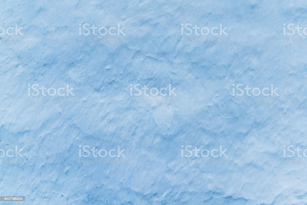 Adobe whitewashed wall in light blue color, traces of brush, background with copy space for text or objects