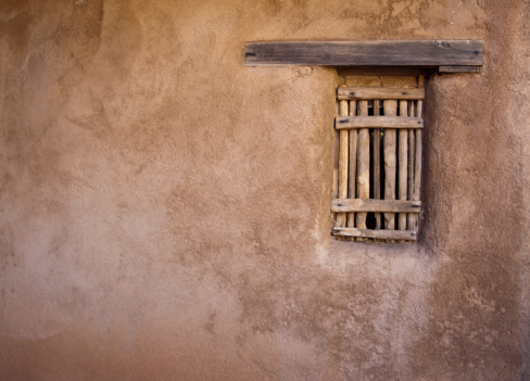 Adobe wall with a window shaded with saguaro ribs.  Plenty of copy space.