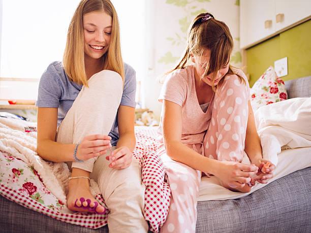 teenager-mädchen im schlafanzug auf dem bett zusammen ihre zehennägel lackieren - nägel lackieren stock-fotos und bilder