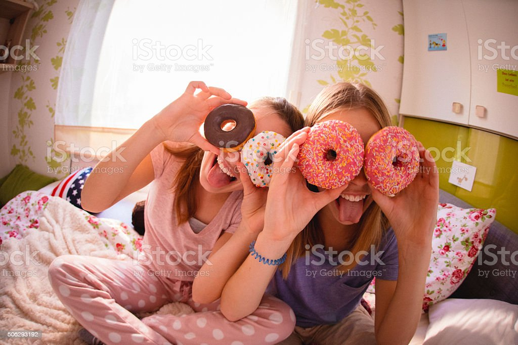 Adolescent girls with colourful doughnuts over their eyes stock photo