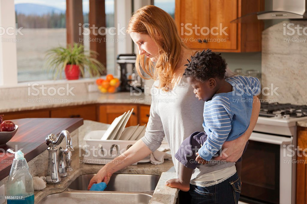 adopted boy watches mother wash dishes royalty-free stock photo