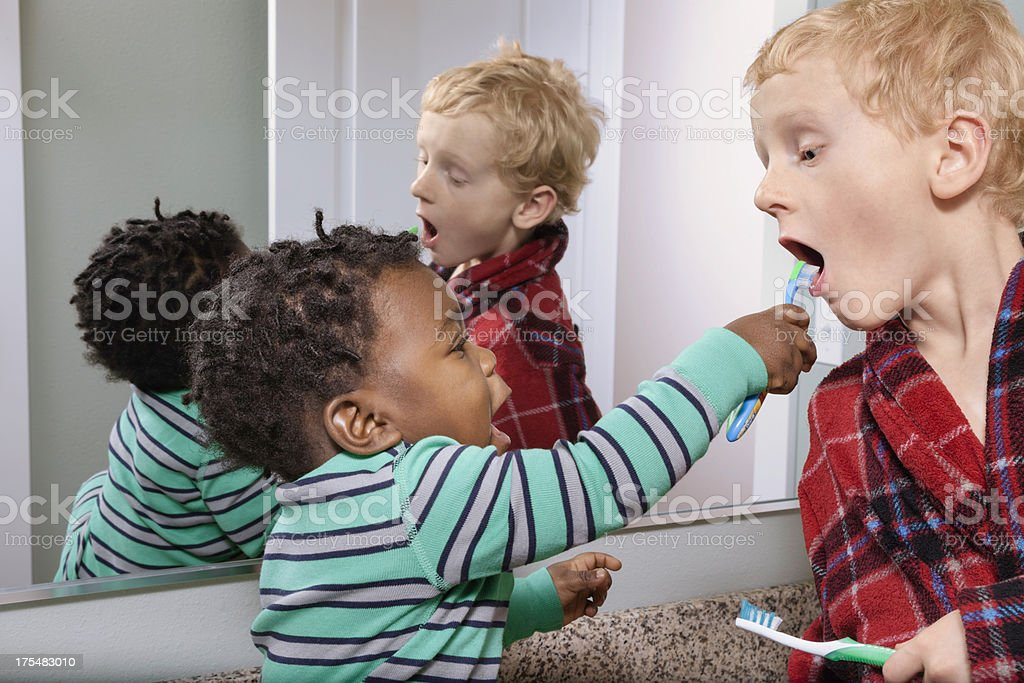 adopted brothers brushing teeth stock photo