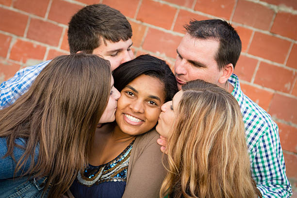 Adopted Daughter Gets Kissed by Loving Family stock photo