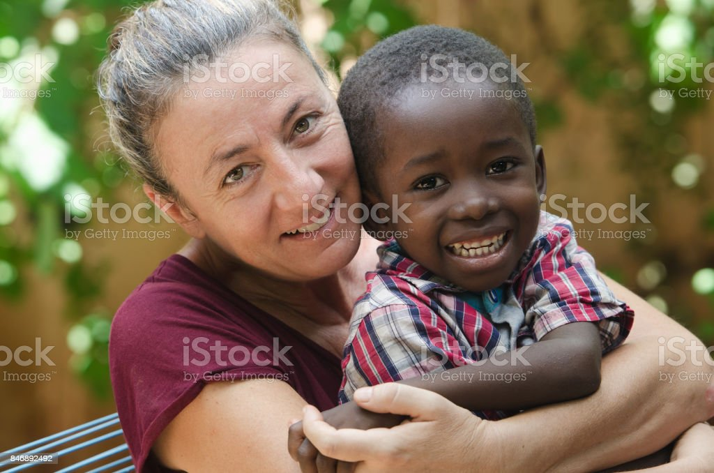 Adoption symbol - Woman adopts a little African boy stock photo