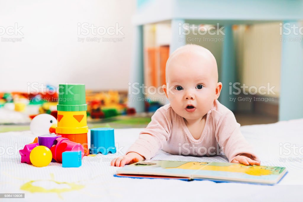 Adorable 6 months old baby looking and reading a book. stock photo