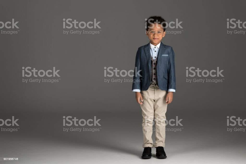 adorable african american boy standing in suit on gray stock photo