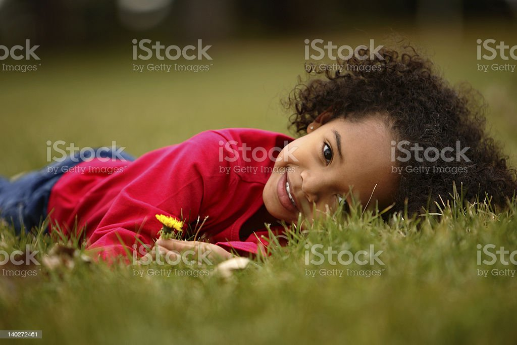 Adorable African American girl laying on grass smiling stock photo