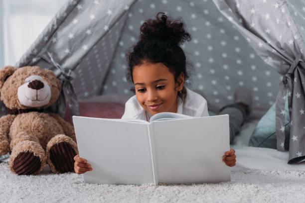 schattig afro-amerikaanse jongen boek lezen en liggen in de tent thuis - a little girl reading a book stockfoto's en -beelden