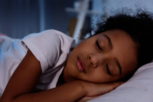 adorable african american kid sleeping in bed at home stock photo