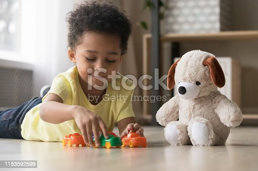 184659330 istock photo Adorable african kid lying on warm floor play with toys 1153592599
