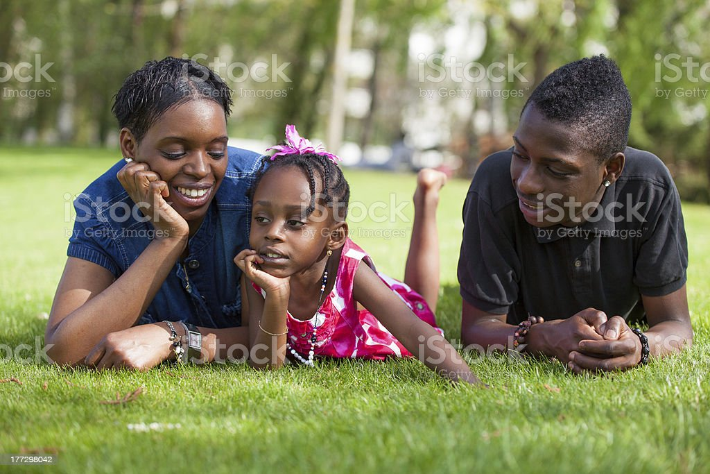 Adorable african mother with her childrens in the garden royalty-free stock photo