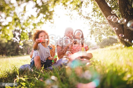 istock Adorable african-american family blows soap bubbles at eachother 518065704