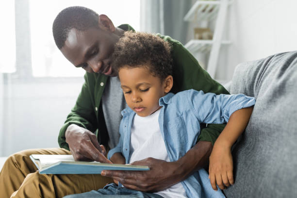 adorable african-american father and son reading book together stock photo