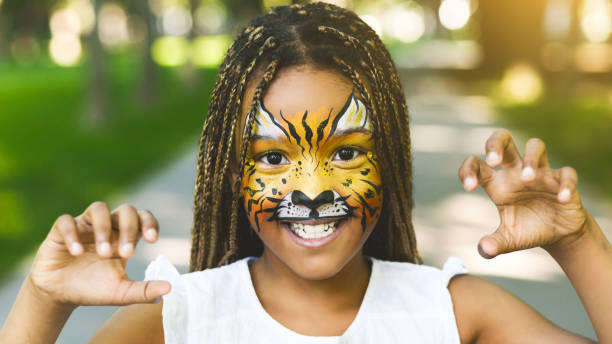 Adorable african-american girl with creative face painting roaring Funny little tiger. Adorable african-american girl with creative face painting roaring, playing wild cat outdoors body paint stock pictures, royalty-free photos & images
